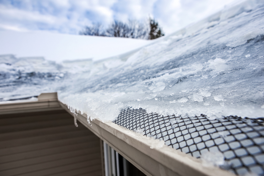 Winter Weather Damage Ice Dam on Roof Gutter